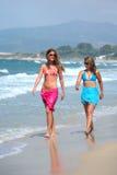 piękna po plaży sandy garbnikującego dwa chodzącej młodą kobietę obraz stock