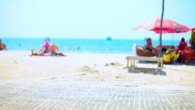 Piękna pogodna ustronna plaża na wakacjach patrzeje nad połówka zakopującym driftwood w piasku z miękkimi ostrość ludźmi i zbiory