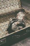 Piękna porcelanowa lala w starej zniszczonej walizce fotografia stock