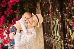 Piękna potomstwo matka trzyma małego w białej bluzce i kapeluszu obrazy royalty free