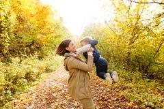 Piękna potomstwo matka z jej synem w jesień lesie fotografia stock