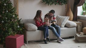 Piękna potomstwo para świętuje w domu Ładna dziewczyna daje jej chłopakowi prezenta pudełku zbiory
