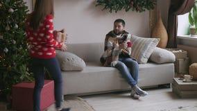 Piękna potomstwo para świętuje w domu Ładna dziewczyna daje jej chłopakowi prezenta pudełku zbiory wideo