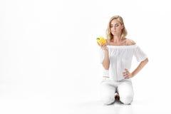 Piękna poważna blondynki kobieta w białych bluzek spojrzeniach przy żółtym dzwonkowym pieprzem Zdrowy łasowanie i dieta Fotografia Royalty Free
