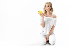 Piękna poważna blondynki kobieta w białych bluzek spojrzeniach przy żółtym dzwonkowym pieprzem Zdrowy łasowanie i dieta Obraz Stock