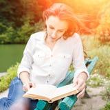 Piękna poważna dziewczyna czyta książkę w zmierzchów promieniach zdjęcie royalty free