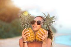 Piękna pozytywna dziewczyna na plaży z ananasami i drzewkami palmowymi z atrakcyjną postacią obraz royalty free