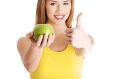 Piękna przypadkowa caucasian kobieta trzyma świeżego zielonego jabłka. Obraz Royalty Free