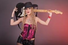 Piękna punkowa dziewczyna z udziałami tatuaże pozuje z gitarą Fotografia Stock