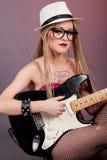 Piękna punkowa dziewczyna z udziałami tatuaże pozuje z gitarą Zdjęcia Royalty Free
