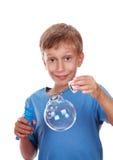 Piękna radosna blond chłopiec dmucha mydlanych bąble w jaskrawej błękitnej koszulce Fotografia Stock