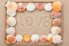 Piękna rama arkana i seashells na piasku z tekst miłością zdjęcia stock
