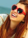 Piękna redhaired dziewczyna w okularach przeciwsłonecznych na plaży, portret obrazy stock