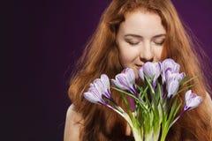 Piękna redheaded kobieta wącha krokusy zdjęcia royalty free