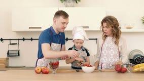 Piękna rodzina przygotowywa wyśmienicie owocowej sałatki w kuchni dom zbiory