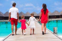 Piękna rodzina w czerwieni ma zabawę na drewnianym jetty Fotografia Royalty Free