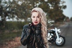 Piękna rowerzysta kobieta plenerowa z motocyklem zdjęcie stock