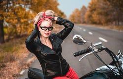 Piękna rowerzysta kobieta pozuje z motocyklem outdoors fotografia royalty free