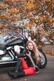 Piękna rowerzysta kobieta pozuje z motocyklem outdoors obrazy royalty free