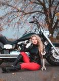 Piękna rowerzysta kobieta pozuje z motocyklem outdoors obrazy stock