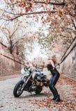 Piękna rowerzysta kobieta pozuje z motocyklem outdoors obraz royalty free