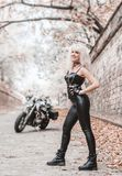 Piękna rowerzysta kobieta pozuje z motocyklem outdoors obraz stock