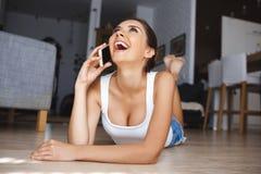 Piękna roześmiana młoda kobieta opowiada na telefonu łgarskim puszku na podłoga w żywym pokoju obrazy royalty free