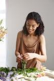 Piękna rozochocona afrykańska dziewczyny kwiaciarnia ono uśmiecha się robić bukietowi w kwiatu sklepie nad biel ścianą Zdjęcie Royalty Free
