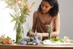 Piękna rozochocona afrykańska dziewczyny kwiaciarnia ono uśmiecha się robić bukietowi w kwiatu sklepie nad biel ścianą Obrazy Royalty Free