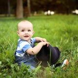 Piękna rozochocona chłopiec z czarnym kapeluszem w lato parku Zdjęcia Royalty Free