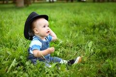Piękna rozochocona chłopiec z czarnym kapeluszem w lato parku Zdjęcia Stock