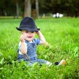 Piękna rozochocona chłopiec z czarnym kapeluszem w lato parku Fotografia Stock