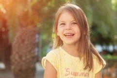 Piękna rozochocona mała dziewczynka jest uśmiechnięta i patrzejąca krzywka fotografia royalty free