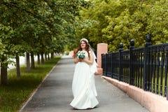 Piękna rozochocona panna młoda patrzeje kamerę w parku w pełnej długości su w białej sukni i przesłona z bukietem w ona ręki zdjęcie royalty free