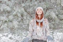 Piękna rozochocona szczęśliwa dziewczyna z czerwonym włosy w kapeluszu ciepłym szaliku i bawić się wokoło i błaź się w śniegu w z Obrazy Royalty Free