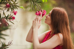 Piękna rudzielec dziewczyna wdycha aromat kwiat Czerwony kwiatu dorośnięcie na drzewie zdjęcia stock
