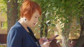Piękna rudzielec kobieta wyszukuje telefon w mieście, boczny widok zbiory