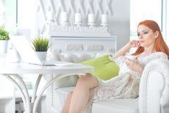Piękna rudzielec młoda kobieta patrzeje laptop i pije herbaty przy lekką kuchnią zdjęcia stock