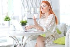 Piękna rudzielec młoda kobieta używa laptop i pijący herbaty przy lekką kuchnią fotografia royalty free