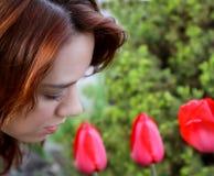 Piękna rudzielec wącha tulipany w ogródzie obraz stock