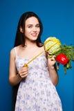 Piękna słodka dziewczyna trzyma centymetra i kapusty w prostej sukni Obraz Stock
