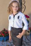 Piękna słodka dziewczyny uczennica w mundurku szkolnym outside na słonecznym dniu z kędzierzawym włosy i wiankiem delikatne róże  Zdjęcia Stock