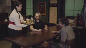 Piękna słodka gruba dziewczyna z trzy szkłami piwo na tacy w piwnej restauracji Kelnerka przynosi piwo dwa faceta zbiory wideo
