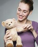 Piękna 20s dziewczyna trzyma jej ulubionego comforter z zabawą dla niewinności i dziecka szczęścia Zdjęcie Stock