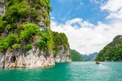 Piękna scena łódź na zieleń jasnego wodzie z rockową górą Zdjęcia Royalty Free