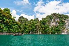 Piękna scena łódź na zieleń jasnego wodzie z rockową górą Obrazy Stock
