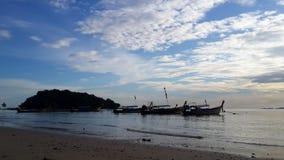 Piękna scena zmierzch przy plażą dopatrywania niebieskiego nieba łódź i światło słoneczne zdjęcie royalty free