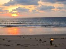 Piękna sceneria przegapia płonącą pochodnię na romantycznej plaży przy zmierzchem zdjęcie royalty free