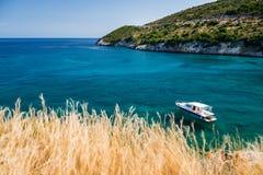 Piękna sceneria z błękitną łodzią i morzem zakotwiczał blisko brzeg Zdjęcie Royalty Free
