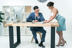 Piękna sekretarka opowiada jej szef przy biurem zdjęcia stock